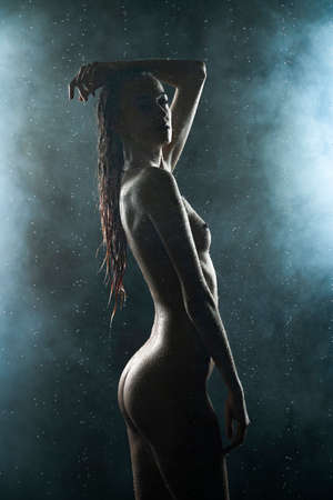 Beautiful silhouette slim wet girl, posing nude in the drops of the rain, in theatrical smoke, in the dark. Artistic, conceptual, lifestyle design Stockfoto