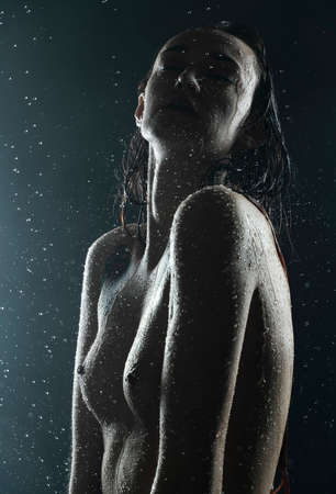 Beautiful silhouette slim wet girl, posing nude in the drops of the rain, in theatrical fog, in the dark. Artistic, conceptual, design. Close Up portrait