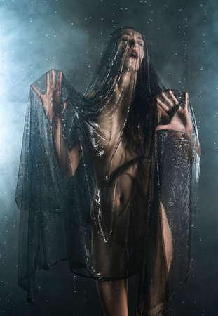 Schönes schlankes nasses Mädchen, das sinnlich im Regen posiert, im Theaterrauch, mit ihrem Körper bedeckt mit schwarzem transparentem Schleier auf dunklem Hintergrund. Kunst, konzeptionelles, modisches Design Standard-Bild