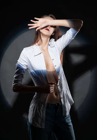 Beautiful slim girl wearing jeans and an unbuttoned shirt poses in a spotlight circle. Creative, conceptual, design