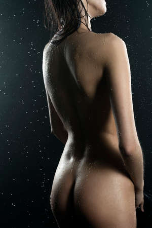 Beautiful slim nude girl, with healthy wet body sensually posing in the rain on black background. Art, commercial design