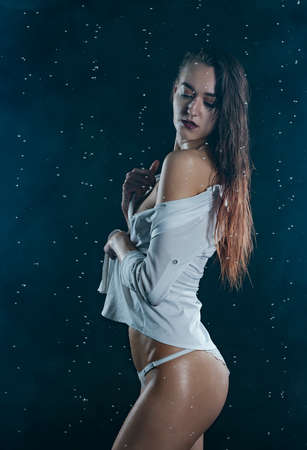 Beautiful wet slim girl wearing panties and an unbuttoned shirt, posing in rain on black background. Artistic, fashionable design