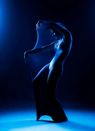 Slim girl wearing a white bodysuit dances a modern avant garde dance, covering her body with elastic transparent fabric in blue light. Artistic, conceptual and creative design. Silhouette photography Reklamní fotografie
