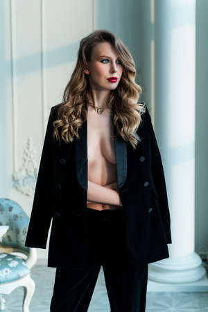 A beautiful slim topless blonde girl with red lips, wearing black pants and unbuttoned blazer, which covers her breast, stands in a vintage interior and looks out the window