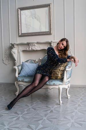 Una bella ragazza bionda snella dalle gambe lunghe con le labbra rosse, che indossa un abito di paillettes, si rilassa sul divano in un lussuoso interno vintage. Stile di vita, design alla moda, commerciale e pubblicitario Archivio Fotografico
