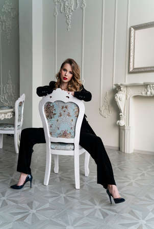 A beautiful slim blonde girl with red lips, wearing black pants and a fashionable blazer, sits on a chair in a luxury vintage interior. Lifestyle, trendy and advertising design Stockfoto