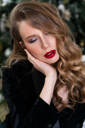 Portrait of a beautiful blonde girl with red lips and evening makeup, wavy hair wearing a black velvet jacket. Healthy, clean skin. Close-up. Advertising, commercial design Stockfoto