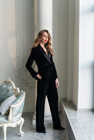 A beautiful slim blonde girl with red lips, wearing black pants and a fashionable blazer, stands at the window in a luxury vintage interior. Lifestyle, trendy and advertising design