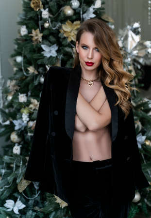 A beautiful slim topless blonde girl with red lips, wearing black pants and unbuttoned blazer, covers her breast with her hands standing in a vintage interior at the christmas tree and smiles