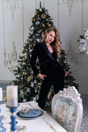 A beautiful slim blonde girl with red lips, wearing black pants and blazer, stands in a luxury vintage interior at the christmas tree and table and smiles Stockfoto