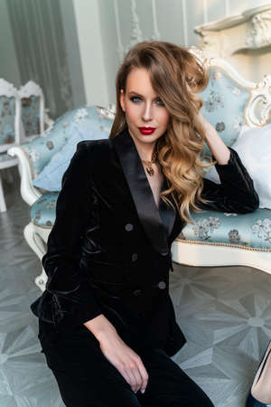 A beautiful slim blonde girl with red lips, wearing black pants and a fashionable blazer, sits on the floor at a sofa in a luxury vintage interior. Lifestyle, trendy and advertising design Stockfoto
