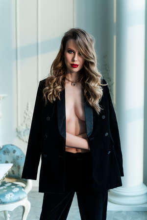 A beautiful slim topless blonde girl with red lips, wearing black pants and unbuttoned blazer, which covers her breast, stands in a vintage interior in the window light