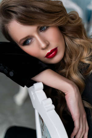 Portrait of a beautiful blonde girl with red lips and evening make-up, wavy hair wearing a black velvet jacket, sitting, leaning on the back of a chair. Healthy, clean skin. Close-up