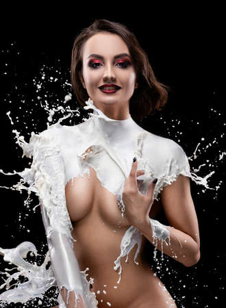 A beautiful smiling brunette girl, dressed in clothes made of splashes and drops of milk on her body, covers her breasts with her hands. Isolated on black. Creative, advertising and art design