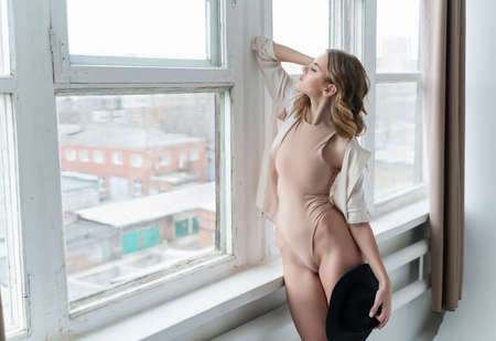 A beautiful leggy girl wearing a bodysuit and unbuttoned shirt, relaxedly stays at the window and holds black hat in her hand. Fashionable, advertising and commercial design Reklamní fotografie
