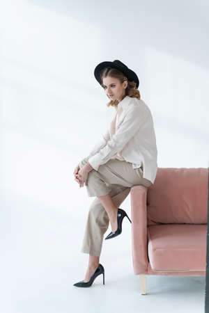 A beautiful girl wearing trousers, an unbuttoned shirt over a bra and a black hat sits thoughtfully and relaxed on a sofa on a white background. Fashionable, advertising and commercial design