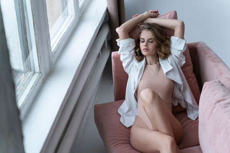 A beautiful girl wearing a bodysuit, open shirt, pensive and relaxedly lies on a sofa by the window. Fashionable, advertising and commercial design Reklamní fotografie