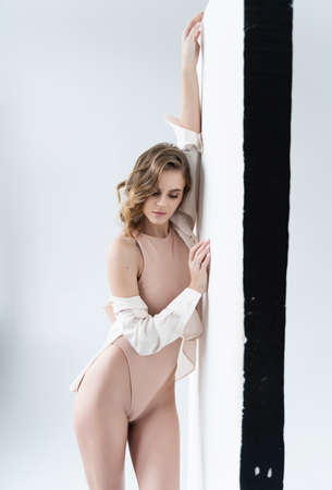 A beautiful leggy girl wearing a bodysuit and unbuttoned shirt, relaxedly stays at the white wall. Fashionable, advertising and commercial design Reklamní fotografie