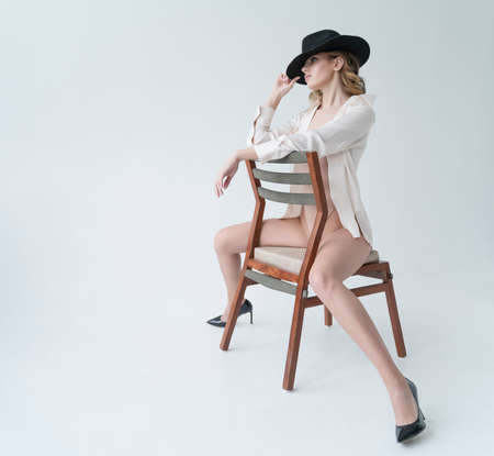 A beautiful leggy girl wearing a bodysuit, black hat and unbuttoned shirt, relaxedly sits on a chair on white background. Fashionable, advertising and commercial design Reklamní fotografie