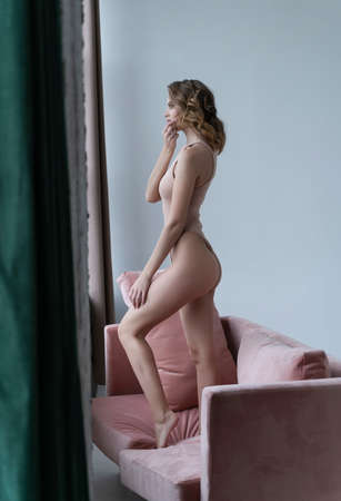 A beautiful leggy girl wearing a bodysuit, open shirt, pensive and relaxedly stays on a sofa by the window and looks outside. Fashionable, advertising and commercial design Reklamní fotografie