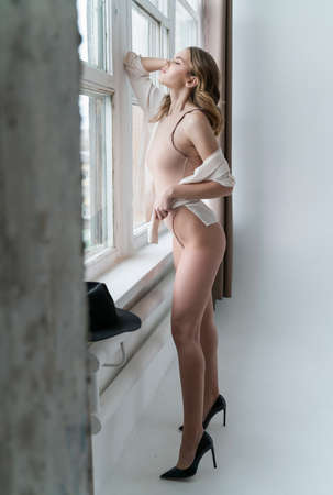 A beautiful leggy girl wearing a bodysuit and unbuttoned shirt, relaxedly stays at the window. Fashionable, advertising and commercial design Reklamní fotografie