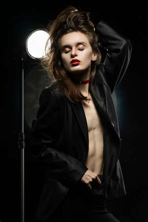 Beautiful braless girl with red lips, wearing an unbuttoned black blazer, touches her hair with her hand on a dark background, posing next to a light lamp. Advertising, trendy, and lifestyle design