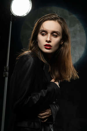 Beautiful slim girl model with red lips, wearing a black blazer, fearfully hugs herself with hands on a dark background, posing next to the light lamp. Advertising, trendy, and lifestyle design