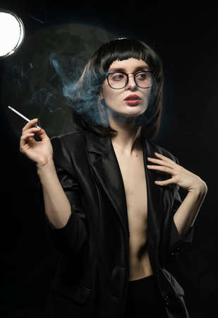 Beautiful braless slim girl with red lips, wearing a unbuttoned black blazer, glasses and brunette wig sensually smokes un a dark background next to the light lamp. Advertising and lifestyle design