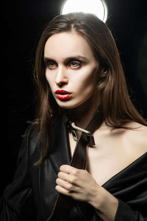 Braless girl with red lips, wearing a black unbuttoned blazer and a mens leather belt tightened around the neck, which she pulls with her hands,  on the dark background, next to a light lamp