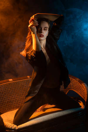 Beautiful braless girl, wearing a unbuttoned blazer, sensually posing dancing on her knees on sofa, on dark background next to the blue and warm light lamp in the theatrical smoke. Noir design