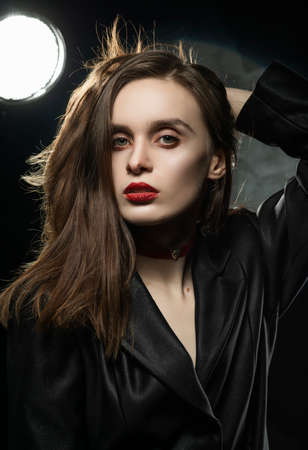Beautiful slim girl model with red lips, wearing a black blazer, touches her hair with her hand on a dark background, posing next to a light lamp. Advertising, trendy, and lifestyle design