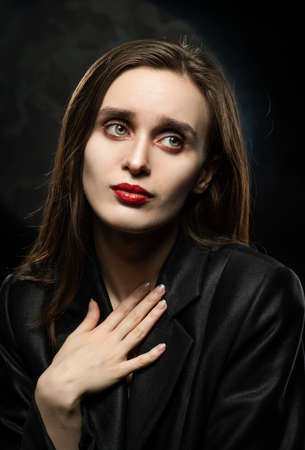 Beautiful slim girl model with red lips, wearing a black blazer, with an apologetic gesture presses her hand to her chest on a dark background, next to the light lamp. Advertising, trendy design Reklamní fotografie