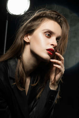 Beautiful braless slim girl, wearing a unbuttoned black blazer, with a slight frenzy and detachment in her eyes touches her face with her hand on a dark background, next to the light lamp
