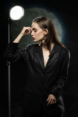 Beautiful slim girl model with red lips, wearing a black blazer, touches her face with her hand on a dark background, posing next to a light lamp. Advertising, trendy, and lifestyle design