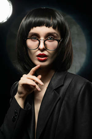 Beautiful braless slim girl with red lips, wearing a unbuttoned black blazer, glasses and brunette wig on a dark background, posing next to the light lamp. Advertising, trendy, and lifestyle design Reklamní fotografie
