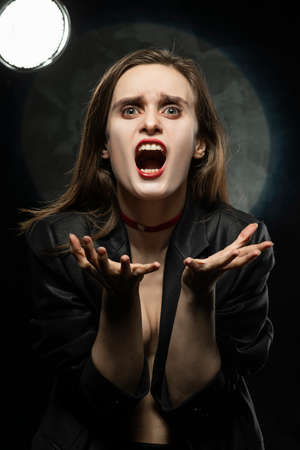 Beautiful braless girl with red lips, wearing a black blazer, screams, stretching forward her hands on a dark background, posing next to a light lamp. Advertising, trendy, and lifestyle design