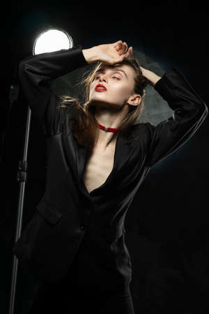 Beautiful slim braless girl, wearing a unbuttoned black blazer, sensually touches her hair with her hand on a dark background, posing next to a light lamp. Advertising, trendy design