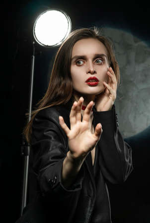 Beautiful slim girl model with red lips, wearing a black blazer, fearfully protects herself with her hand on a dark background, next to the light lamp. Advertising, trendy, and lifestyle design