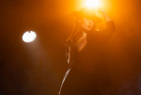 Beautiful braless actress girl, wearing an unbuttoned blazer and a hat, poses and dances in the warm light rays of scenic illuminators in the theatrical fog. Noir, lifestyle and trendy design Reklamní fotografie