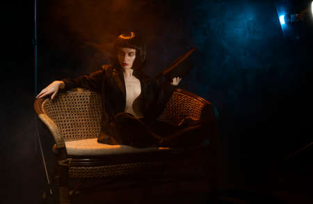 Beautiful braless slim girl, wearing unbuttoned black blazer, and brunette wig, posing on sofa holding a hat in her hand next to the blue and warm light lamp in the theatrical smoke. Noir design Reklamní fotografie