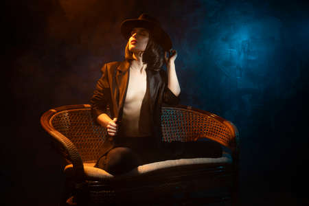 Beautiful braless girl, wearing a unbuttoned black blazer, brunette wig and hat, sensually posing on sofa on dark background next to the blue and warm light lamp in the theatrical smoke. Noir design Reklamní fotografie