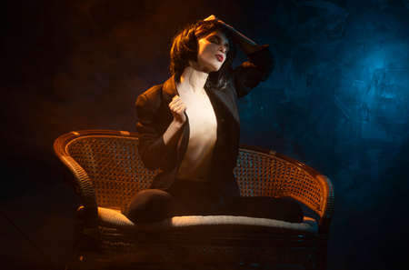 Beautiful braless girl, wearing a unbuttoned blazer, sensually pulls off a brunette wig from her head, on dark background next to the blue and warm light lamp in the theatrical smoke. Noir design Фото со стока