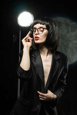 Beautiful braless slim girl with red lips, wearing a unbuttoned black blazer, glasses and brunette wig on a dark background, posing next to the light lamp. Advertising, trendy, and lifestyle design Фото со стока