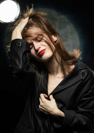 Beautiful braless slim girl, wearing a unbuttoned black blazer, with an expression of suffering on her face raises hair with her hand on a dark back ground, next to the light lamp