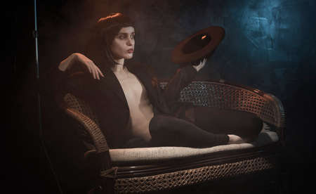 Beautiful braless slim girl, wearing unbuttoned black blazer, and brunette wig, posing on sofa holding a hat in her hand next to the blue and warm light lamp in the theatrical smoke. Noir design Фото со стока