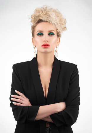 A beautiful blonde girl with an elegant hairstyle and large breasts, wearing a bra, trousers and a blazer, poses isolated on white. Trendy, commercial and advertising design 免版税图像