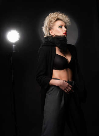 A beautiful blonde girl with an elegant hairstyle and large breasts, wearing a bra, trousers, scarf and a blazer, fashinable poses near the spotlight. Trendy, commercial and advertising design