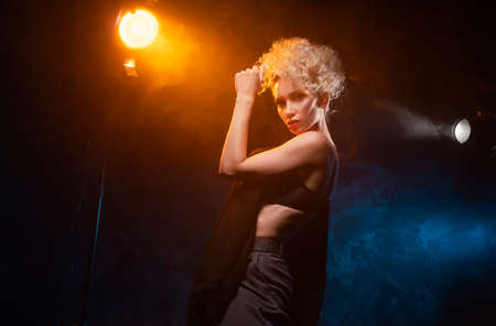 A beautiful blonde girl with an elegant hairstyle and large breasts, wearing a bra, trousers and a blazer, artistically poses in the rays of spotlights in the smoke. Cinematic, art, commercial design
