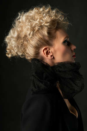 A beautiful blonde girl with an elegant hairstyle and large breasts, wearing a bra, scarf and a blazer, poses in the dark. Trendy, commercial and advertising design. Close Up portrait 免版税图像