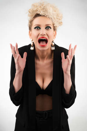 A beautiful blonde girl with an elegant hairstyle and large breasts, wearing a bra, trousers and a blazer, screams hysterically on white. Trendy, commercial and advertising design.